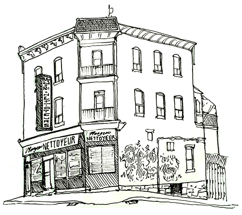 A rundown brick building with one corner angled off, and signs on the front and corner declaring Nettoyeur. The building is on a slight slope, three stories high, with two apartments above the shop. The apartments have two windows in front, three on the side, and a small balcony on the corner. The back of the building has a fence and a plastic-covered balcony. There is graffiti and wiring along the side.